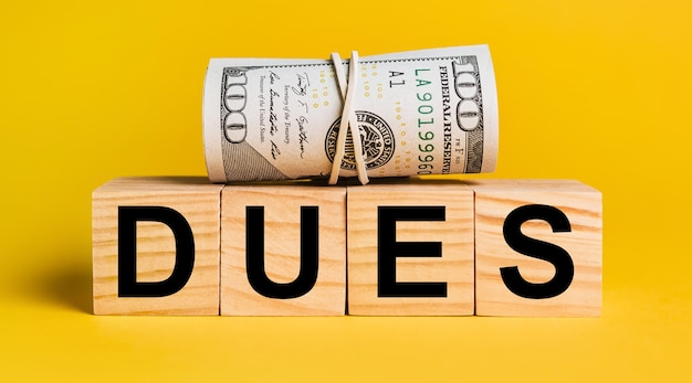 Dues with money on a yellow background. the concept of business, finance, credit, income, savings, investments, exchange, tax