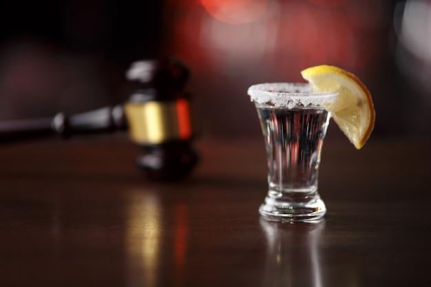 飲酒運転の概念法ガベルアルコールと木製の机の上の車の鍵