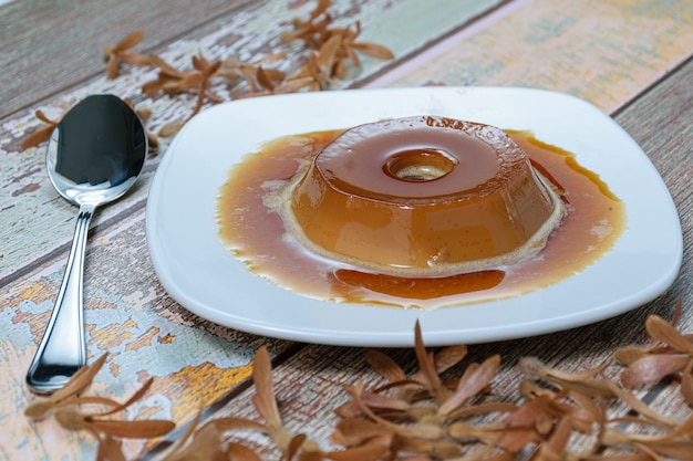Пудинг dulce de leche с карамельным соусом, рядом с ложкой и летающими семенами (triplaris americana). традиционная бразильская сладость.