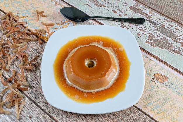 Dulce de leche pudding with caramel syrup, alongside flying seeds (triplaris americana). a traditional brazilian sweet.