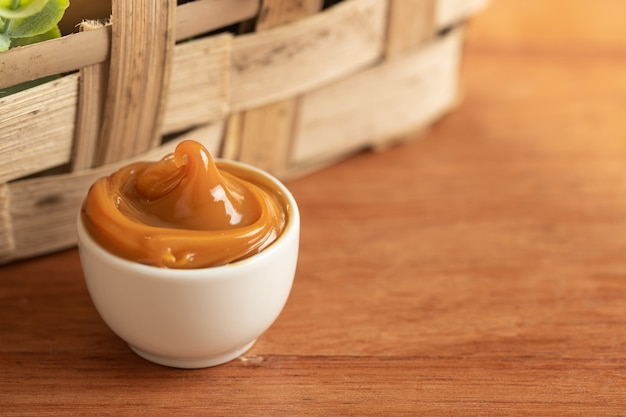 Dulce de leche in a white container on a wooden table.