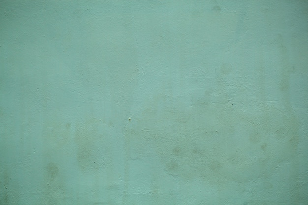 Dull forest green painted wall  texture with a close up on the surface in a full frame view.