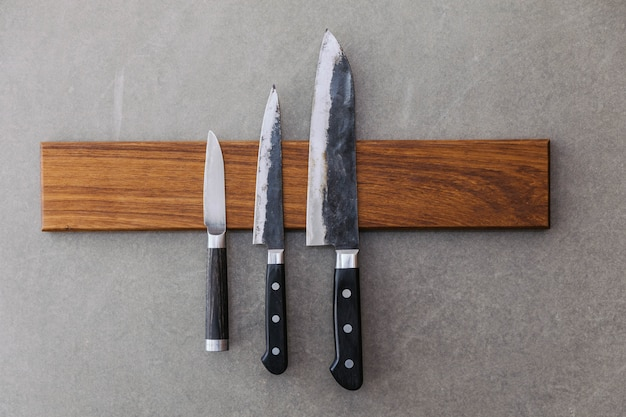 Dull japanese kitchen knives stick on magnet cover with wood on concrete wall.