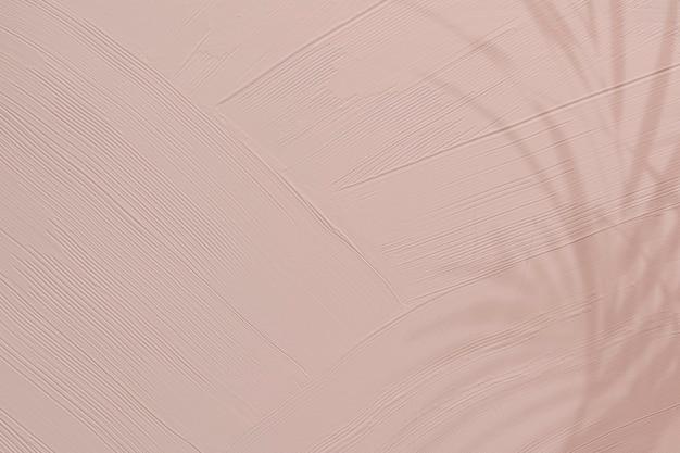 葉の影と鈍いピンクのペイントテクスチャ