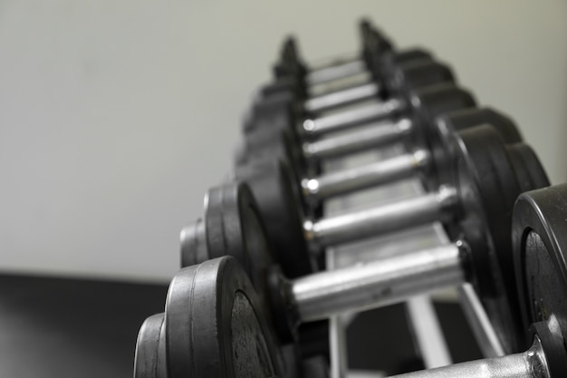 Dumb bells lined up in a fitness studio. picture is short focus