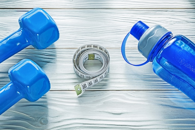 Dumb-bells rolled measuring tape water bottle on wooden board fitness concept
