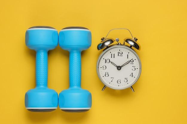 ダンベル、黄色の目覚まし時計