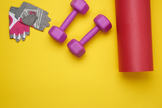 ダンベルとスポーツグローブ、ヨガスポーツ用のツイストネオプレンマット、黄色の表面