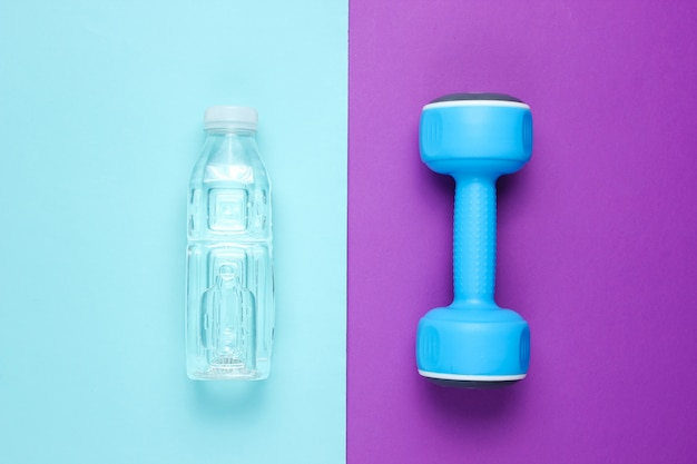 Dumbbell, bottle of water on colored surface.