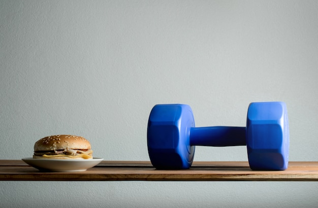 Dumbbell and burger on wood table diet, exercises for weight loss concept.