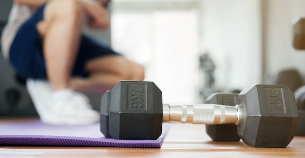 Dumbbell exercise on mat with man resting after workout to build muscle at home gym in the morning