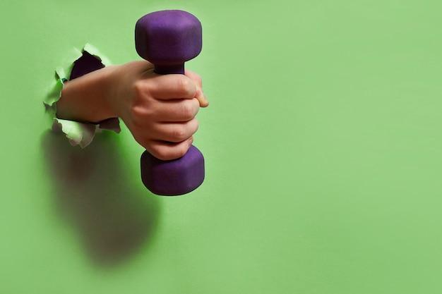 緑の紙の穴を通して手にダンベル。アクティブなライフスタイル、健康、スポーツのコンセプト。