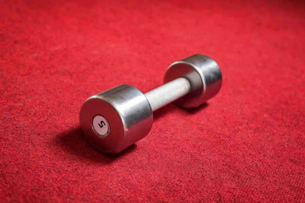 The dumbbell lies on a red background