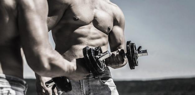 Гантель. парни мускулистые бодибилдеры, упражнения с гантелями. сильный бодибилдер, идеальные дельтовидные мышцы, плечи, бицепсы, трицепсы и грудь. мышцы с гантелями. тренировка человека с гантелями.