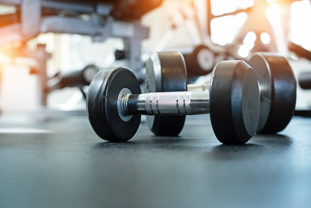 The dumbbell put on ground floor, at fitness gym, blurry light around