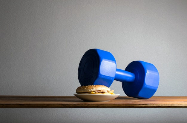 Dumbbell put on hamburger idea exercises for weight loss diet concept.