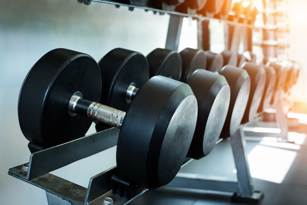 The dumbbell set stacked on rack, at fitness gym, warm light tone, blurry light around