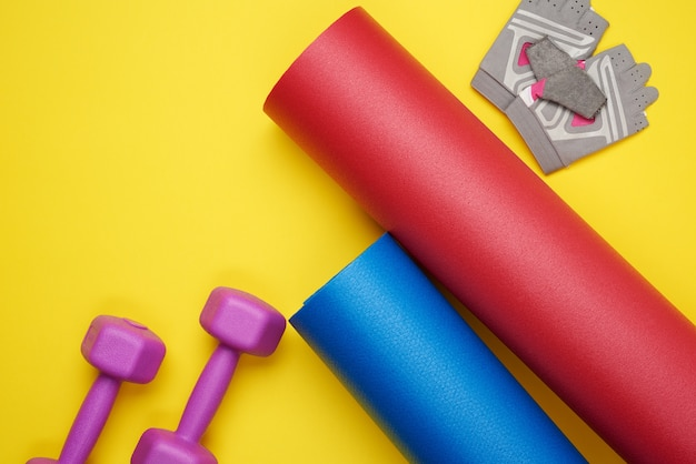 Dumbbell and sports gloves, twisted neoprene mat for yoga sport on yellow surface