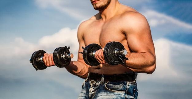 Гантели сильный культурист идеальные дельтовидные мышцы плеч бицепсы, трицепсы и грудь