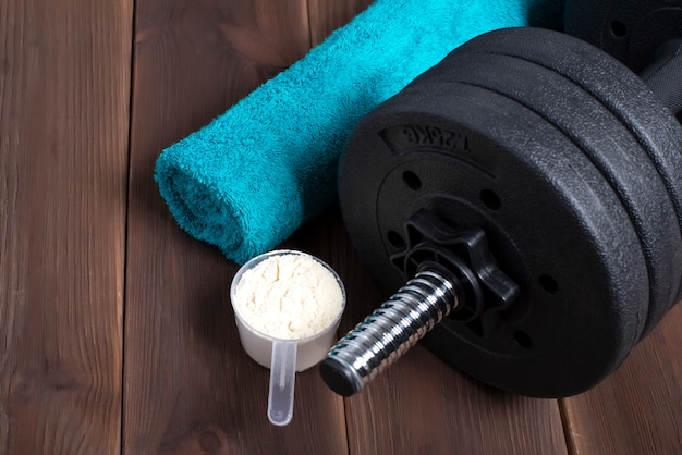 Dumbbell and supplements on wooden floor. fitness background with blue towel.