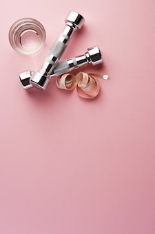 Dumbbell and tape measure with drinking water on pink surface
