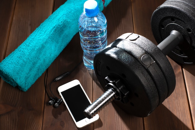 Dumbbell, water bottle, blue towel, telephone, headphones on the wooden floor of the gym.