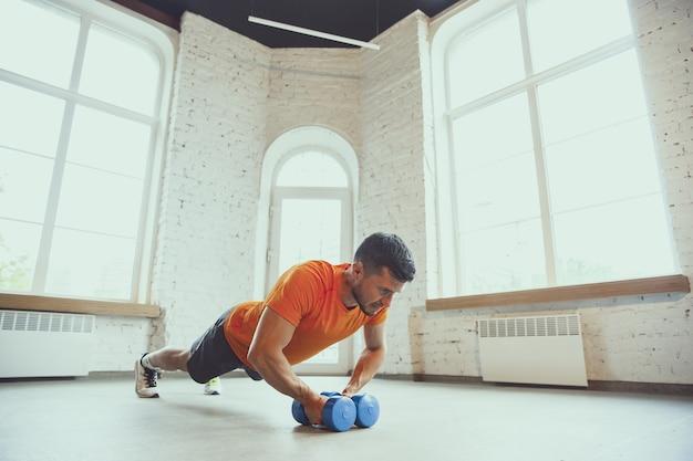 ダンベル。コロナウイルスの発生の検疫中に自宅でトレーニングし、フィットネス、有酸素運動を行う若い白人男性。断熱中にスポーティーな状態を保ちます。ウェルネス、スポーツ、運動の概念。