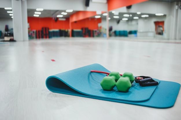 Гантели и спортивный коврик в тренажерном зале