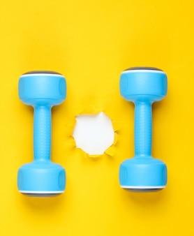 Гантели и рваные дыры в желтой бумаге. минималистичный фитнес-концепция. вид сверху