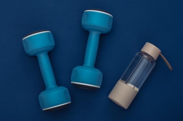 古典的な青い背景にダンベルと水筒。健康的なライフスタイル、フィットネストレーニング。カラー2020。上面図