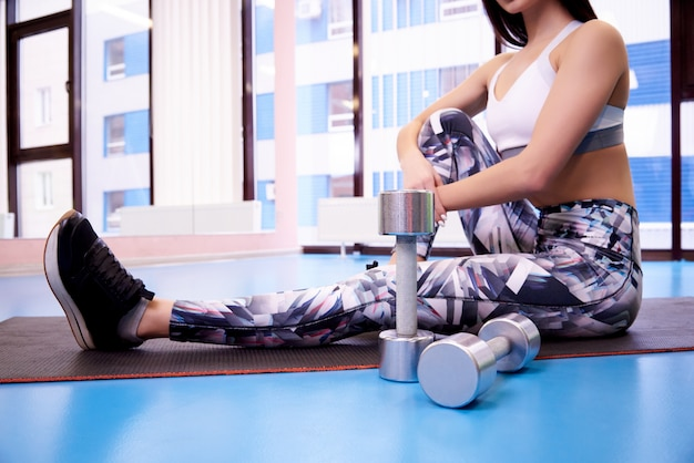 Dumbbells on the background of a young woman in the gym.