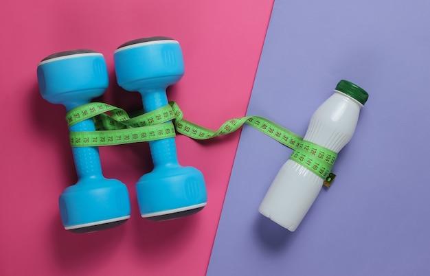 Dumbbells, bottle of kefir, measuring tape on colored paper