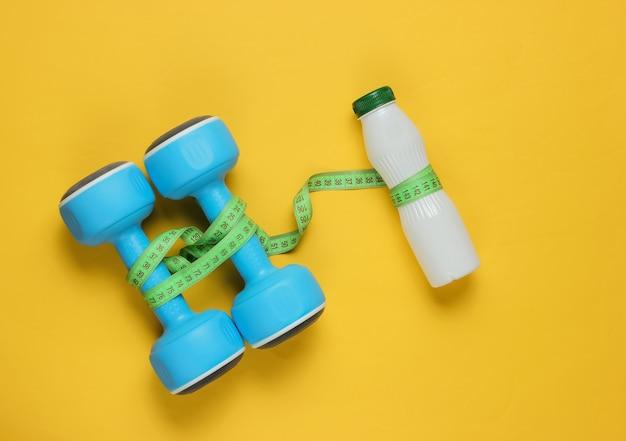 Dumbbells, bottle of kefir, measuring tape on yellow paper