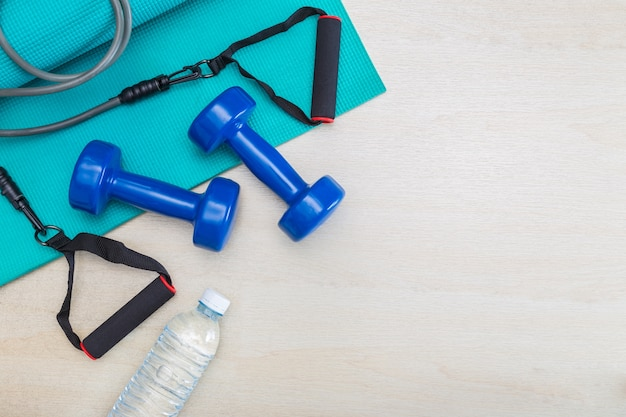 Dumbbells, excercise equipment, gym yoga mat, and bottle of water on clean wood floor