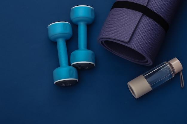 クラシックな青い背景にダンベル、フィットネスマット、ウォーターボトル。健康的なライフスタイル、フィットネストレーニング。カラー2020。上面図。フラットレイ
