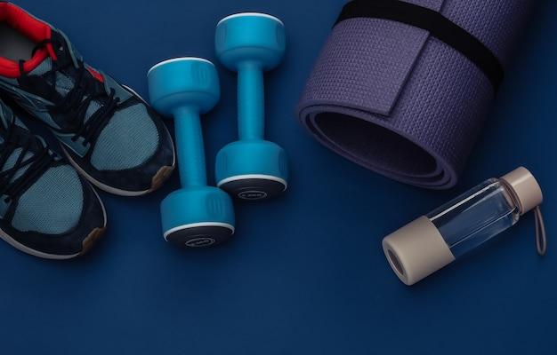 クラシックな青い背景にダンベル、フィットネスマット、ウォーターボトル、スニーカー。健康的なライフスタイル、フィットネストレーニング。カラー2020。上面図。フラットレイ