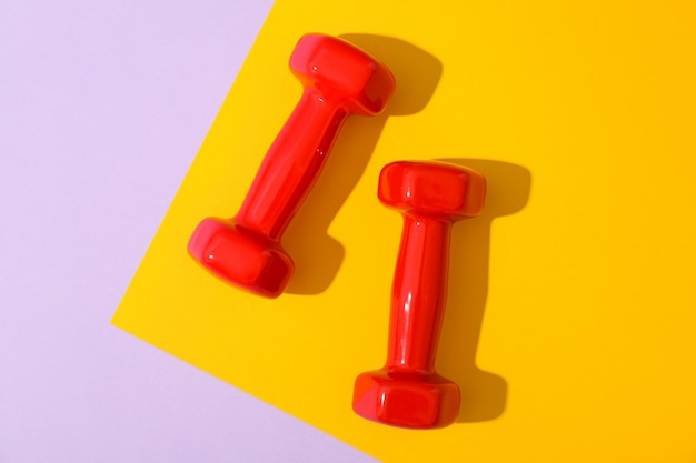Dumbbells for fitness on two tone background, space for text
