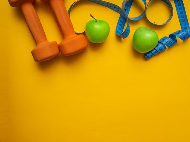 Гантели для фитнеса, яблоки и измерительная лента на желтом фоне. концепция похудения. flatlay, copyspace.