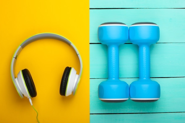 Dumbbells and headphones on blue wooden table