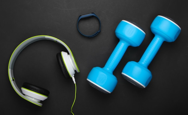 Dumbbells, headphones, smart bracelet, wate on black surface