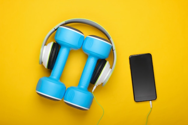 Dumbbells and headphones with smartphone on yellow surface