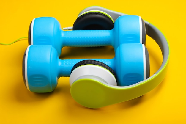 Dumbbells and headphones on yellow surface