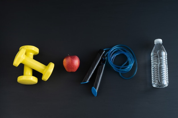 Dumbbells and jump rope on black background for home exercise. copy space.