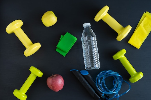 Dumbbells and jump rope on black background.