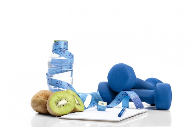 Dumbbells, kiwi, measuring tape and water bottle