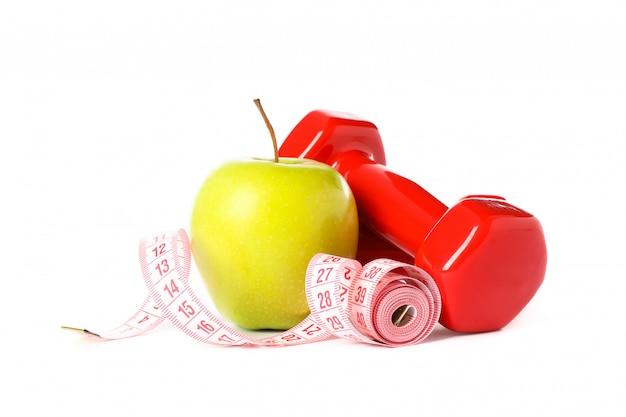 Гантели, измерительная лента и яблоко, изолированные на белом