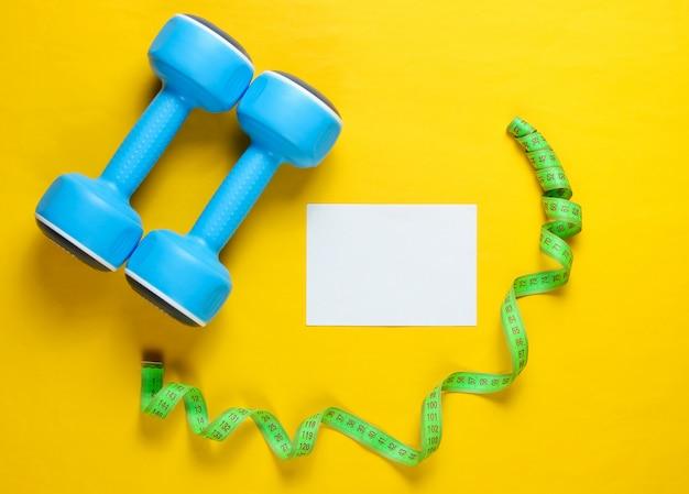 ダンベル、測定テープ、黄色の表面に空白のカード