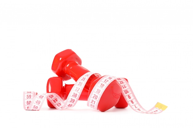 Dumbbells and measuring tape isolated on white