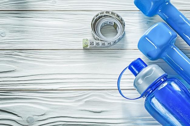 Гантели мерная лента бутылка с водой на деревянной доске фитнес-концепции