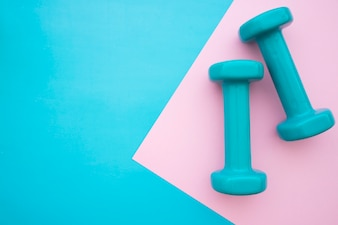 Dumbbells on blue and pink background